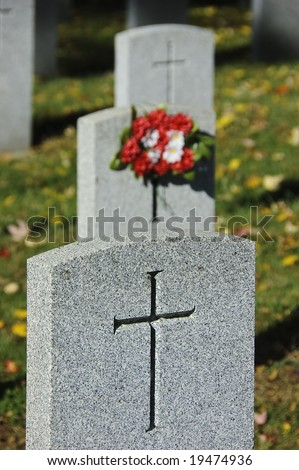 Row of three soldier tombstones marked with crosses and bouquet of red and white flowers on grassy field