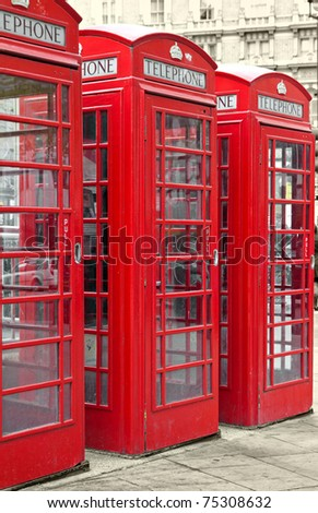 Row of three typical London phone booths with a desaturated background - stock photo