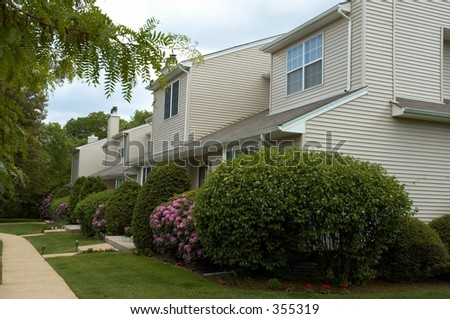 row of townhouses  with green lawn and flowers - stock photo