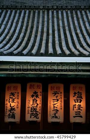 Row of traditional Japanese lanterns under the temple roof - stock photo
