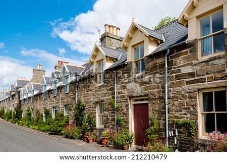 Row of traditional stone houses in a scottish village in front of great cloudy sky - stock photo