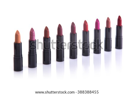 Row of trendy lipsticks, isolated on white background with natural reflection