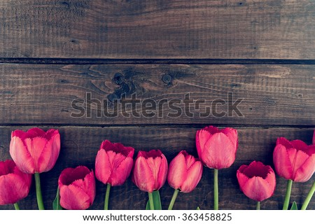 Row of tulips on wooden background with space for message.  Mother's Day background. Top view - stock photo