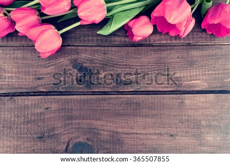 Row of tulips on wooden background with space for message.  Mother's Day background. Top view.
