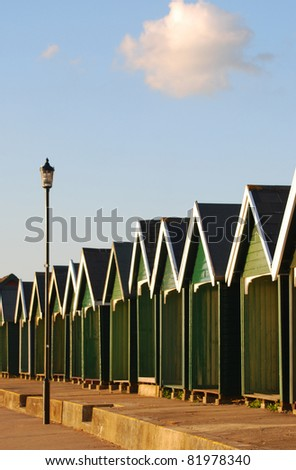 Row of typical british summer beach houses along the Solent beaches in Gurnard, Isle of Wight, United Kingdom - stock photo