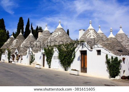 Row of typical trulli houses in Alberobello, Puglia, Italy. Traditional symbols are painted on the conical roofs. A trullo is a traditional Apulian stone dwelling in Itria Valley.  - stock photo