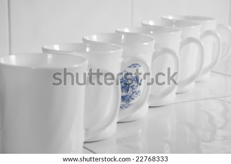 row of uniform white cups with blue pattern on one cup, on ceramic table in cafe - stock photo