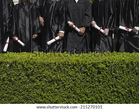 Row of university students in graduation gowns holding diplomas, mid-section, hedge in foreground - stock photo
