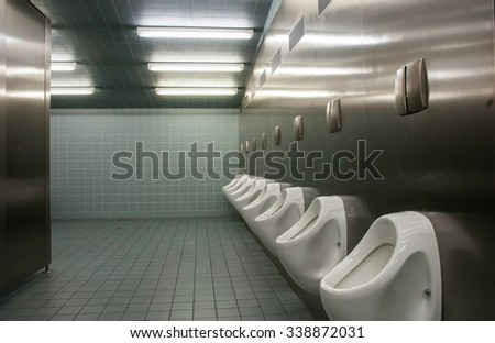 Row of urinal in a public restroom - stock photo
