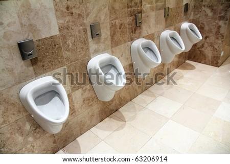 row of urinals in empty clean restroom - stock photo