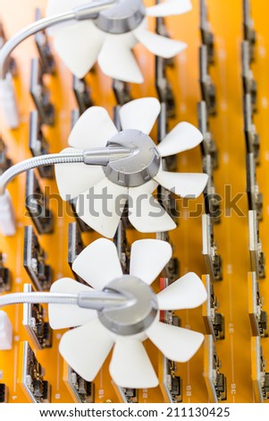 Row of USB bitcoin miners plugged into large USB board. - stock photo
