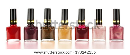 Row of varied red tone nail polish bottles over a white background - stock photo