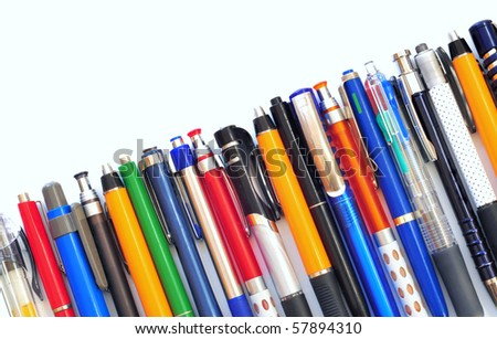 Row of various multicolored ball pens on white background