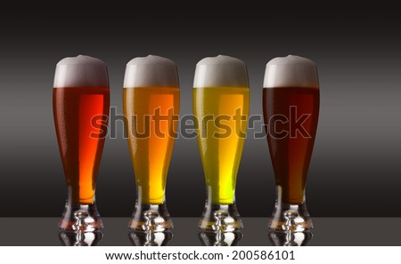 Row of various types of beer with foam - stock photo