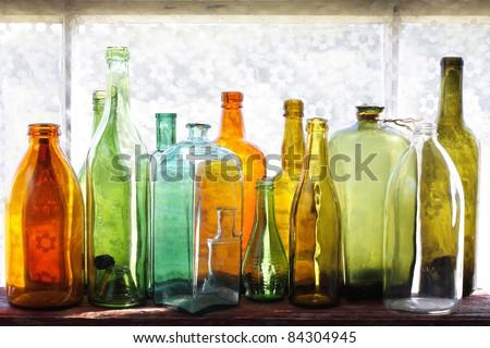 Row of vintage multicolored bottles on a windowsill - stock photo