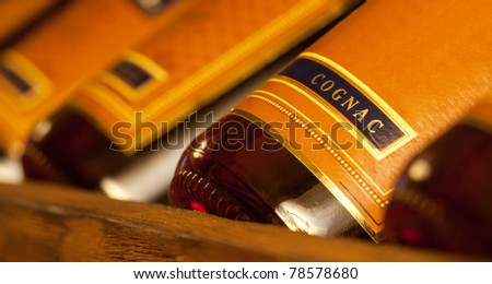 Row of wealth cognac bottles in cellar - stock photo