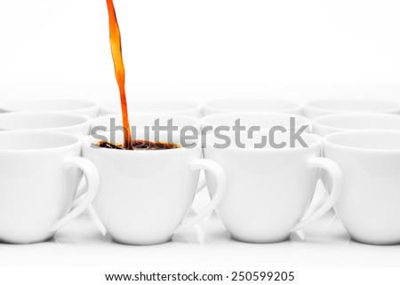 row of white coffee cups with one being filled with hot coffee - stock photo