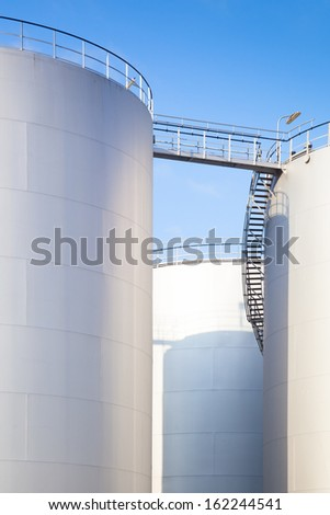 row of white diesel oil tanks of a refinery under a blue sky  - stock photo