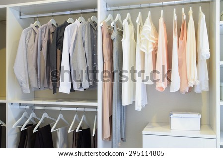 row of white dress and shirts hanging in white wardrobe - stock photo