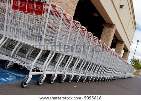 Row of white shopping carts in front of a shopping center - stock photo