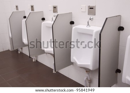 row of white toilets in a man restroom - stock photo