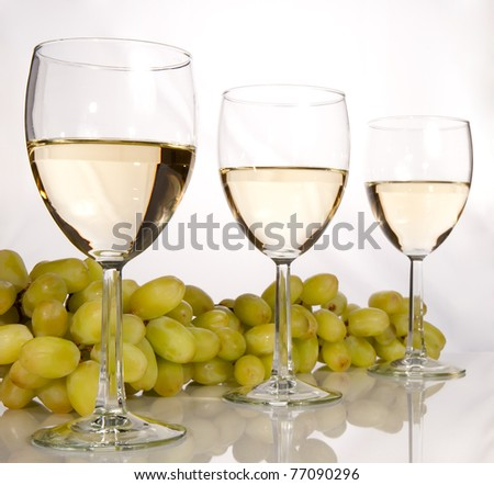 Row of white wine glasses and grapes - stock photo