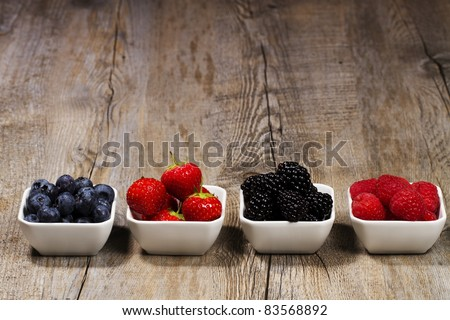 row of wild berries in bowls on wooden background - stock photo