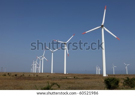 Row of wind turbines against a blue sky