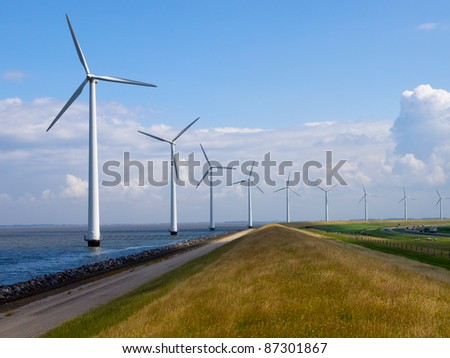 Row of wind turbines along motorway - stock photo