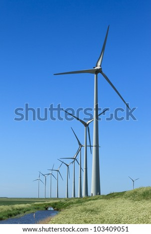 Row of wind turbines in the countryside near the Eemshaven, Holland. - stock photo