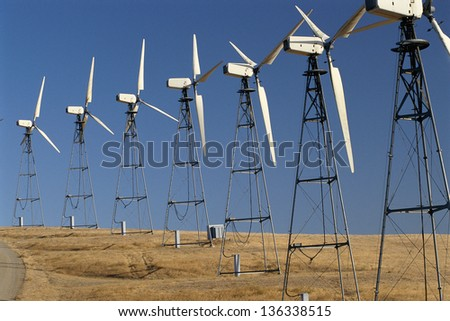 Row of wind turbines on a wind farm - stock photo