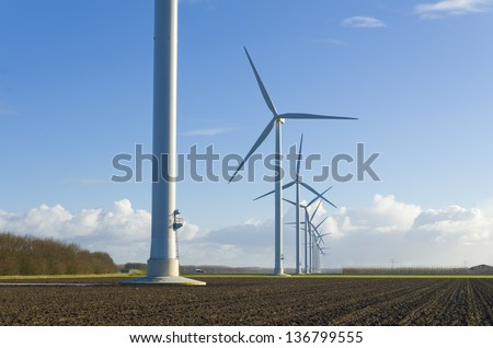 row of windmills in an agricultural landscape in the netherlands - stock photo