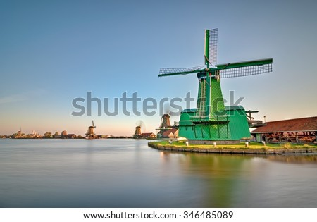 Row of windmills on the water channels in Netherland - stock photo