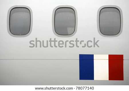 Row of windows of a passenger plane with the flag of France - stock photo