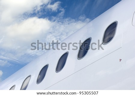 Row of Windows of an Airplane against blue sky - stock photo