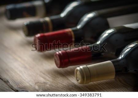 Row of wine bottles on the wooden table . Low depth of field.