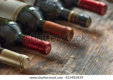 Row of wine bottles with dry red  wine on wooden background. Low depth of field.  - stock photo