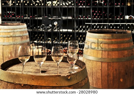Row of wine glasses on barrel in winery cellar - stock photo