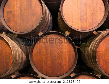 Row of wooden barrels of tawny portwine ( port wine ) in cellar, Porto, Portugal - stock photo