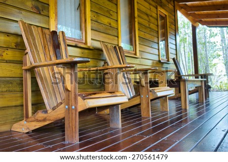 Row of wooden chairs on chalet terrace. - stock photo