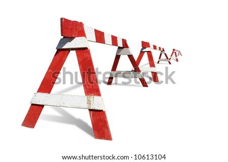 Row of wooden red and white striped road construction barriers - isolated on white - stock photo