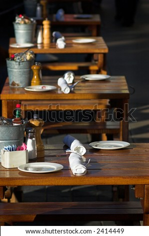 Row of wooden tables at a sidewalk cafe - stock photo