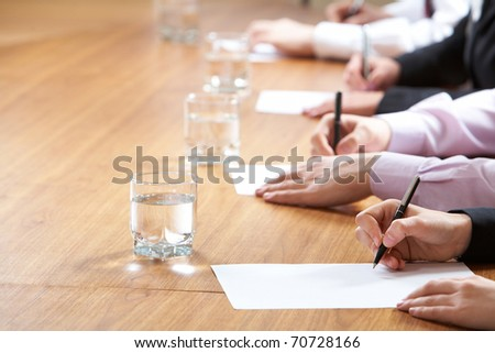 Row of writing hands on table - stock photo