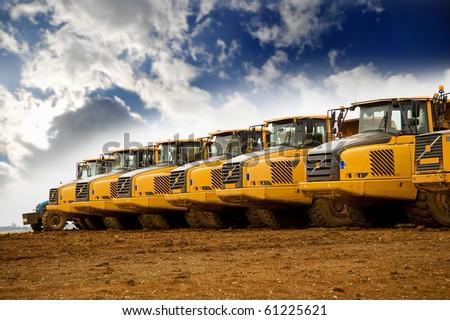 Row of yellow heavy tipper trucks - stock photo