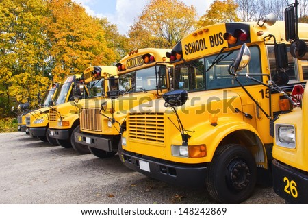 Row of yellow school buses against autumn trees - stock photo