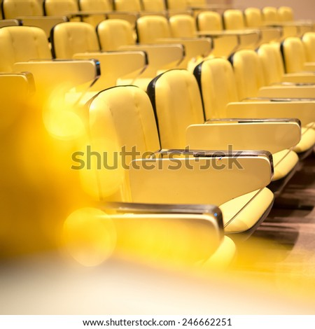 Row of yellow seat in auditorium - stock photo