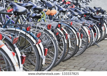 Row parked bicycles in Amsterdam - stock photo