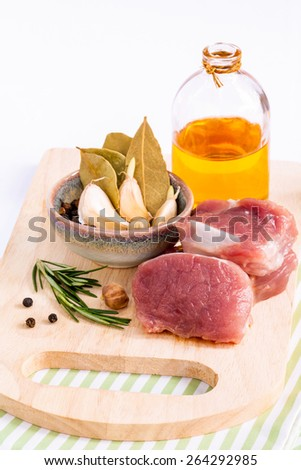 Row pork tenderloin with herbs on cutting board. - Steak preparing and ingredients. - stock photo