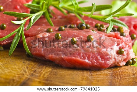 Row Steak whit green pepper and rosemary on plate of wood - stock photo