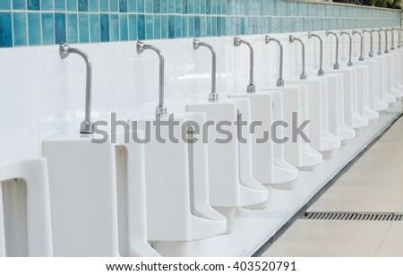 Row urinals in public toilet. - stock photo